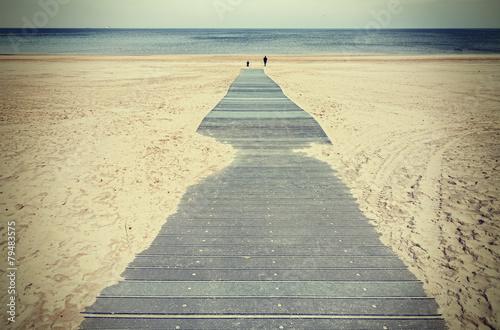 Retro toned photo of a boardwalk on beach. - 79483575