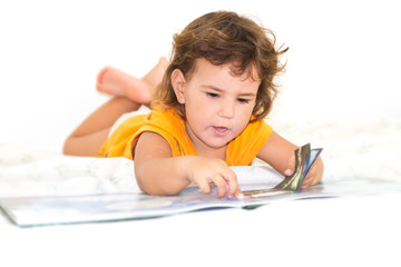 indoor portrait of cute child girl reading a book at home