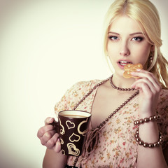 Young woman drinking latte and eating cookie. Toned.
