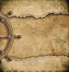 steering wheel and torn vintage nautical map
