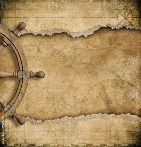 steering wheel and torn vintage nautical map - 79484163