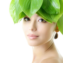 Beautiful young cheerful woman. Girl with green leaves near her