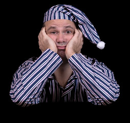 unhappy man in pajamas on a black background