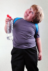 schoolboy with a bottle of water making faces