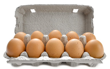 Cardboard egg box with ten brown eggs isolated on white.