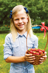 cute girl holding a basket of ripe strawberries