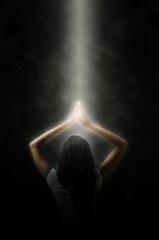 Portrait einer meditierenden Frau in einem Lichtstrahl