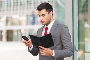 Businessman using his mobile phone while holding an agenda