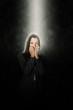 Ängstliche Frau steht alleine in einem Lichtstrahl