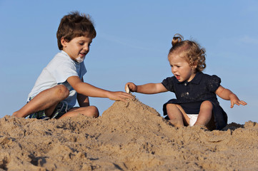 Two children have fun on the beach playing with the sand.