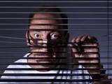 Vicious man looking sideways through venetian blind - 79489951