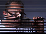 Vicious man looking sideways through venetian blind poster