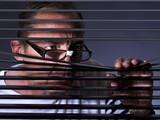 Vicious man looking sideways through venetian blind - 79489998