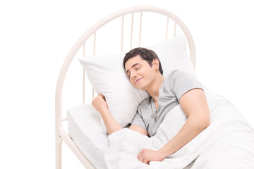 Carefree young man sleeping in a comfortable bed
