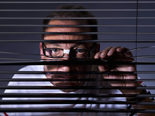 Vicious man looking sideways through venetian blind