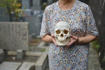お墓で頭蓋骨を持っている老人