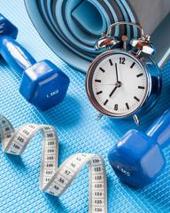Yoga mat, two dumbbells, tape measure and alarm clock.