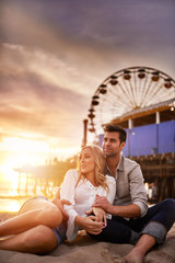 romantic couple relaxing on beach at santa monica