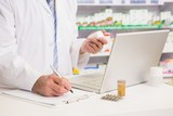 Pharmacist writing on clipboard and holding medication poster