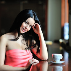 Beautiful girl sitting at the restaurant with a cup of tea or co