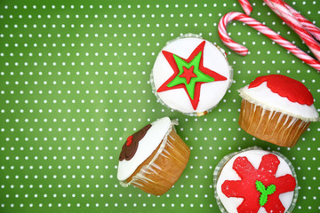 Festive Christmas cupcakes and candy canes on green background
