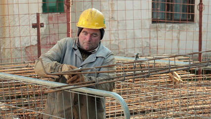 Worker tied reinforcement with plier at construction site