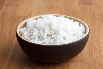 Rustic bowl of white rice on modern wood surface.