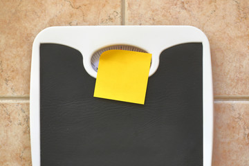 Bathroom scale with blank memo sticker. Diet and fitness concept