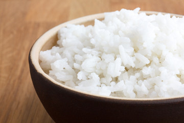 Rustic bowl of white rice on wood surface. Detail.