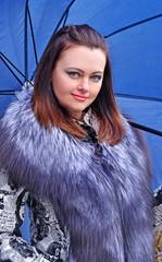 Mujer estilo fashion con un abrigo de piel y paraguas.