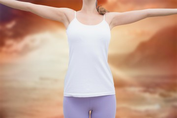 Woman standing with arms raised on countryside
