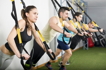 People at gym doing trx elastic rope exercises