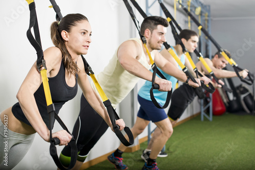 People at gym doing trx elastic rope exercises - 79496327