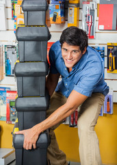 Man Carrying Stacked Toolboxes In Hardware Store
