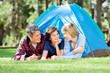 Smiling Family Camping In Park