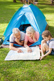 Grandparents With Granddaughter Studying Map At Campsite
