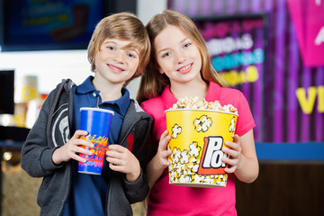 Happy Brother And Sister Holding Snacks At Cinema