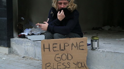 Homeless woman begging and smoking cigarette