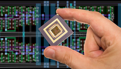 Microprocessor in hand in front of chip layout