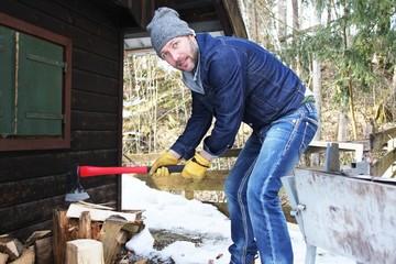 Mann beim Holz hacken im Winter