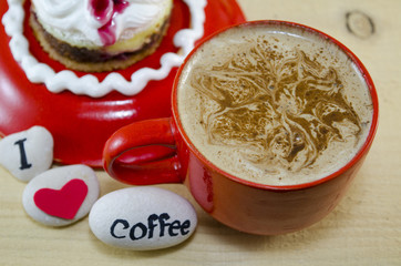 Red cup of coffee with decorated foam
