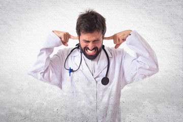 Doctor covering his ears over white background