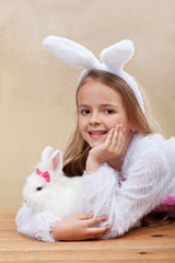 Happy girl in bunny costume holding her white rabbit