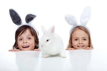 Kids with their white rabbit pet