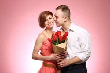 Portrait of romantic man giving flowers to woman, emotions happy