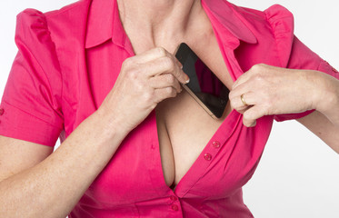Blond woman tucking mobile phone into her bra for safe keeping
