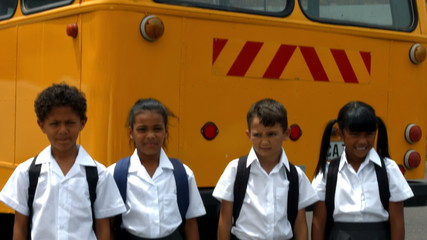 Cute pupils showing thumbs up by bus