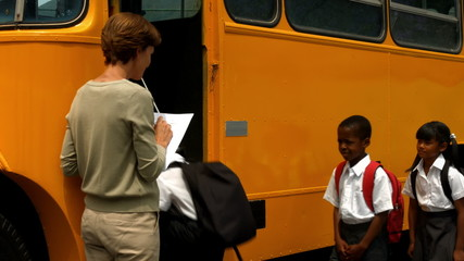 Teacher checking list of pupils by bus