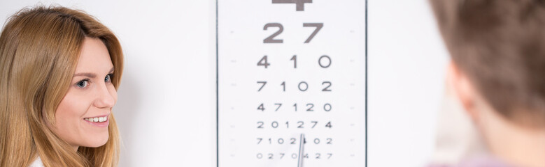 Optician using Snellen test