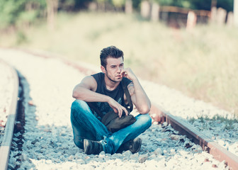 young man sitting on a railroad tracks